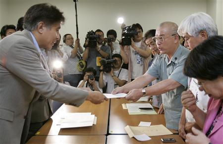 Akio Maejima (3rd R), a lawmaker from Japan's southern island of Okinawa, hands a statement over to an education ministry official in Tokyo June 22, 2007. REUTERS/Toru Hanai