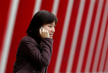 A woman speaks on her phone outside an office building in Beijing in a file photo. Global mobile phone use will top 3.25 billion -- equivalent to around half the world's population -- in 2007 as cell phone demand booms in China, India and Africa, a survey said on Wednesday. REUTERS/Jason Lee
