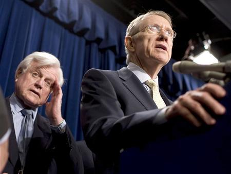 Senator Edward Kennedy (D-MA) (L) wipes his face as Senate Majority Leader Harry Reid (D-NV) speaks at a press briefing after the Immigration bill failed to move past closure in the U.S. Senate on Capitol Hill in Washington June 28, 2007. REUTERS/Joshua Roberts