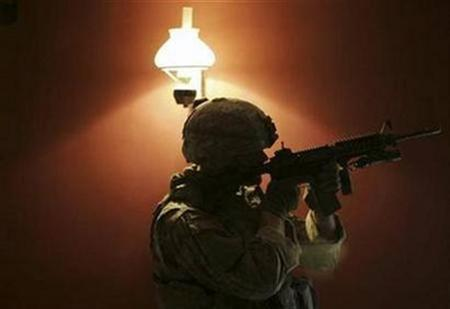 A U.S. soldier stands guard inside a house during an operation in the Sunni neighbourhood of Al-Jamia in Baghdad, in this May 27, 2007 file photo. Five U.S. soldiers were killed in a roadside bomb attack on their patrol in Baghdad, the U.S. military said on Friday, bringing this month's death toll for American forces in Iraq close to 100. REUTERS/Eduardo Munoz