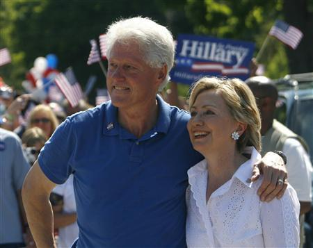 Democratic Presidential candidate and Senator Hillary Clinton (D-NY) and her husband, former President Bill Clinton, smile to supporters during the 4th of July parade in Clear Lake, Iowa, July 4, 2007. REUTERS/Joshua Lott