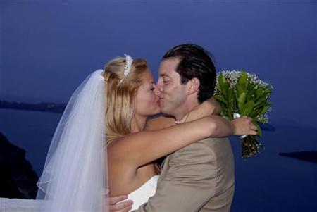 Andrew Speaker, a 31-year-old attorney, kisses his wife Sarah Cooksey during their wedding ceremony on the Greek island of Santorini May 18, 2007. Passengers who were aboard a flight with the U.S. tuberculosis patient in May launched nine civil lawsuits against him on Thursday, claiming that he knowingly exposed them to the disease. REUTERS/Stringer