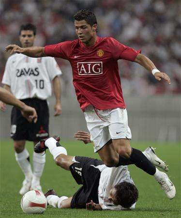 England's Manchester United midfielder Cristiano Ronaldo (R) battles for the ball with Japan's Urawa Reds midfielder Hideki Uchidate (bottom) during their friendly match in Saitama, north of Tokyo July 17, 2007. REUTERS/Yuriko Nakao