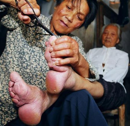 A 105-year-old woman, who has bound feet, has her toenails cut by her daughter in Jiukou county of Zhongxiang city in central China's Hubei province June 28, 2006. Foot binding, which aims to make a woman's feet look tiny and therefore desirable, was practiced in China for centuries before it was banned in 1912 at the fall of the last imperial dynasty. REUTERS/Ge Gong