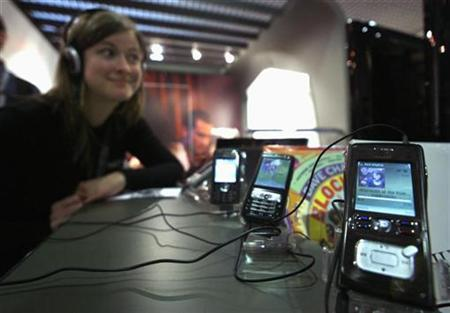 A woman listens to music on a cell phone in a file photo. While young people embrace the Web with real or virtual friends and their cell phone is never far away, relatively few like technology and those that do tend to be in Brazil, India and China, according to a survey. REUTERS/Eric Gaillard