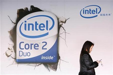 A woman checks her mobile phone as she walks past an Intel Core Duo advertisement outside a computer shop in Beijing March 26, 2007. The European Commission issued formal charges against Intel on Thursday for allegedly using illegal tactics against smaller rival Advanced Micro Devices (AMD), according to people familiar with the situation. REUTERS/Claro Cortes IV