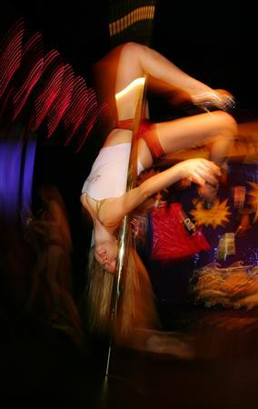 A woman pole dances at a booth run by a pole dancing school in Sydney in this July 28, 2005 file photo. At an hour when its teenage viewers ought to be sleeping, a music video channel has been broadcasting a few titillating minutes of the latest contest to excite Italian television. REUTERS/Tim Wimborne