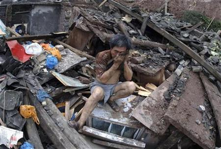 Zheng Kaifu grieves as he sits amid the ruins of his house after a flood hits Sanhui town, China, July 9, 2007. The world experienced a series of record-breaking weather events in early 2007, from flooding in Asia to heatwaves in Europe and snowfall in South Africa, the United Nations weather agency said on Tuesday. REUTERS/China Daily