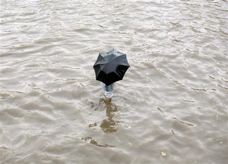 A man wades through a flooded road after heavy rainfall in the western Indian city of Ahmedabad August 8, 2007. REUTERS/Amit Dave