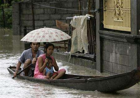 People sit in a boat along a flooded street in San Agustin village, Candaba town, in Pampanga province north of Manila August 9, 2007. Homes and farmland drowned in increasingly severe floods are affecting some 500 million people a year and straining relief efforts, a senior U.N. official said.. REUTERS/Darren Whiteside