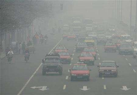 Chinese commuters make their way in heavy smog in Beijing, December 14, 2004. The biggest emissions-cutting projects under the Kyoto Protocol on global warming have directly contributed to an increase in the production of gases that destroy the ozone layer, a senior U.N. official says. REUTERS/Reinhard Krause/Files