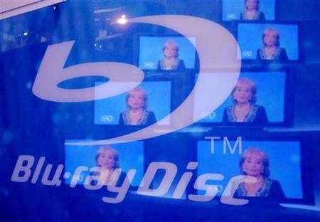 Television images are reflected on a sign for Blu-ray Discs at the 2007 International Consumer Electronics Show (CES) in Las Vegas, January 9, 2007. Blu-ray high-definition movie discs outsold films on the rival HD-DVD format by 2-to-1 in the United States in the first half of 2007, Home Media Research said on Tuesday. REUTERS/Rick Wilking