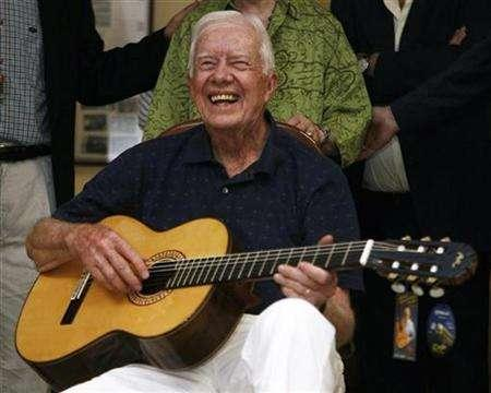 Former U.S. president Jimmy Carter smiles as he holds a Spanish classical guitar in a factory in Esquivias, central Madrid, August 13, 2007. Carter is coming to movie theaters in a documentary centered on his controversial book about the Middle East. REUTERS/Sergio Perez
