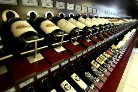 Wine bottles sit on a rack in a store in this undated file photo. The European Union has opened a tender to sell unwanted wine in four countries for use in making bioethanol, its Official Journal said on Tuesday. REUTERS/ Files