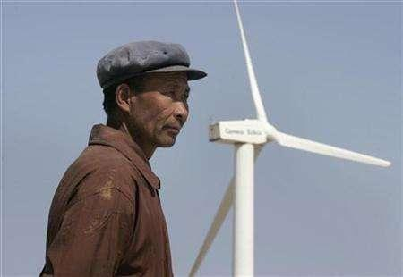 A man stands in front of a windmill at the Gansu Jieyuan Wind Power Company on the outskirts of Yumen, northwest China's Gansu province April 29, 2007. China plans to invest 2 trillion yuan ($265 billion) in renewable energy by 2020, most of it corporate cash, to wean itself off polluting coal as it aims for cleaner growth, a top energy planner said on Tuesday. REUTERS/Jason Lee (