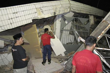 A resident and firefighters look at a damaged building after a strong earthquake struck in Padang, Indonesia's West Sumatra province September 12, 2007. REUTERS/Singgalang- Muhammad Fitrah