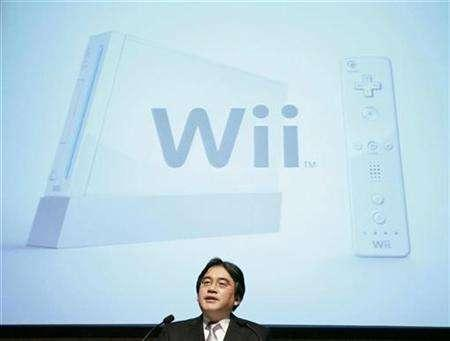 Nintendo President Satoru Iwata speaks at an earnings news conference in front of a screen showing the company's Wii game console in Tokyo April 27, 2007. Nintendo Co Ltd's Wii videogame console outsold Sony Corp's PlayStation 3 by more than four to one in Japan in April-September, game magazine publisher Enterbrain said on Monday. REUTERS/Michael Caronna