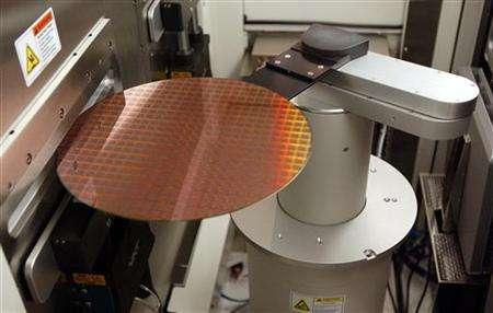 A wafer is loaded into a machine at a manufacturing plant in East Fishkill, New York on March 24, 2004. U.S. electronic companies with combined annual sales of $160 billion urged Congress on Wednesday to approve four pending free trade agreements, which they said were vital to continued economic growth. REUTERS/Chip East