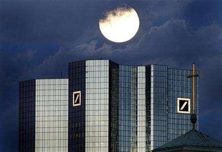 A rising full moon is seen over the distinctive twin towers of Germany's Deutsche Bank headquarters in Frankfurt, January 28, 2002. The Deutsche Bank, the world's third largest business bank will present its annual figures on Thursday, January 31. Government efforts to tackle climate change are creating a ''megatrend'' investment opportunity that should tempt even those skeptical about the nature and pace of global warming, Deutsche Bank analysts said on Thursday. REUTERS/Kai Pfaffenbach