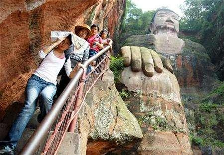 Visitors walk down steps beside the Leshan Giant Buddha statue in Leshan in southwest China's Sichuan province August 29, 2005. Chinese authorities will give a ''facelift'' to the world's tallest stone-carved Buddha just six years after the last repair effort as they struggle to fend off the effects of pollution and crowds, state media reported. REUTERS/China Newsphoto