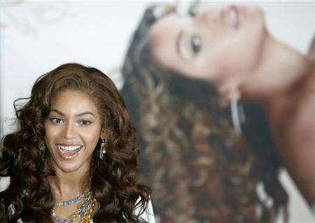 Beyonce Knowles smiles in front of her picture upon her arrival at Incheon international airport, west of Seoul November 8, 2007. REUTERS/Han Jae-Ho