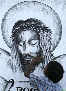 An East Timorese child touches a mural of Jesus Christ during a Easter mass at a church in Dili April 8, 2007. There's no mention of him in the Bible but the plot of a fantasy film set in India gives Jesus Christ a twin brother -- and an evil one at that. REUTERS/Beawiharta