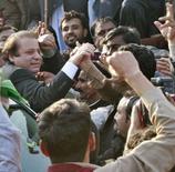 <p>Один из лидеров пакистанской оппозиции Наваз Шариф (слева) приветствует своих сторонников по прибытии в Исламабад 3 декабря 2007 года. Избирательный комитет Пакистана отказала бывшему премьер-министру страны Навазу Шарифу в возможности принять участие в президентских выборах 8 января 2008 года из-за его судимостей. (REUTERS/Mian Khursheed)</p>