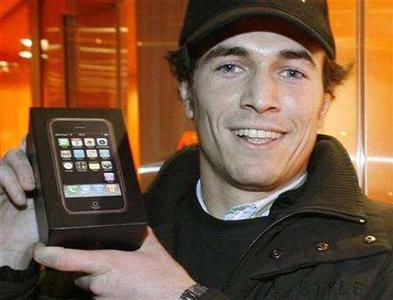 Simon Treille, the first customer to purchase an iPhone in the French capital, displays his handset as hundreds of eager buyers lined up in front of Orange's boutique on Paris' Champs Elysees November 28, 2007. REUTERS/Benoit Tessier