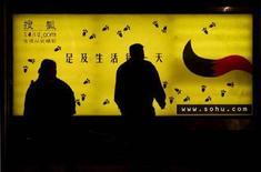 <p>Pendolari in attesa dell'autobus a Pechino davanti ad una pubblicità del portale Sohu.com. ASW/TAN</p>
