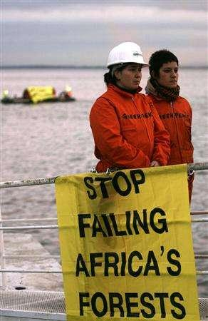 Greenpeace activists show protest banners in front of the UE-Africa summit pavilion in Lisbon December 7, 2007. Greenpeace urged European Union and African leaders meeting in Lisbon over the weekend to take urgent measures to stop the destruction of African forests which cause carbon emissions responsible for climate change. REUTERS/Jose Manuel Ribeiro