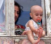 <p>Азербайджанские беженцы в окне своего дома в Баку 12 июля 2000 года. Евросоюзу и не входящим в него странам Европы следует прилагать больше усилий к разрешению конфликтных ситуаций в Кавказско-Каспийском регионе, сообщила Кавказско-Каспийская комиссия в четверг. (STR/REUTERS)</p>