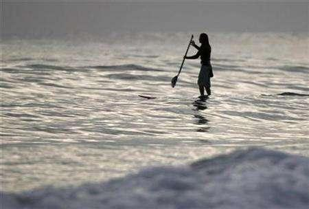 A stand up paddle surfer heads out into the Pacific Ocean to catch a wave after sunset near Solana Beach, California June 27, 2007. REUTERS/Mike Blake
