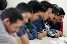 <p>Alcuni immigrati compilano dei moduli. REUTERS/Edgard Garrido</p>