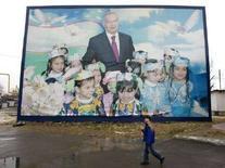 <p>Мальчик идет мимо портрета президента Узбекистана Ислама Каримова в Ташкенте, 23 декабря 2007 года. Центризбирком Узбекистана признал состоявшимися президентские выборы, победу на которых, как ожидается, одержит действующий глава государства Ислам Каримов, баллотирующийся на третий срок вопреки Конституции. REUTERS/Shamil Zhumatov (UZBEKISTAN)</p>
