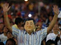 """<p>Сторонник """"Партии народной власти"""" в маске экс-премьера Таиланда Таксина Чинавата во время предвыборной борьбы в Бангкоке, 21 декабря 2007 года. """"Партия народной власти"""" (PPP), объединяющая сторонников экс-премьера Таиланда Таксина Чинавата, получила наибольшее количество мест в ходе проходящих парламентских выборов, согласно данным двух экзит-поллов. REUTERS/Chaiwat Subprasom (THAILAND)</p>"""