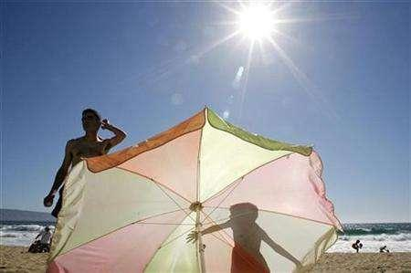 A boy casts a shadow on a sunshade as he stands next to his father on a beach in Vina del Mar city, 85 miles (137 km) northwest of Santiago, December 28, 2006. 2008 will be slightly cooler than recent years globally but will still be among the top 10 warmest years on record since 1850 and should not be seen as a sign global warming was on the wane, British forecasters said. REUTERS/Eliseo Fernandez