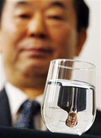 North Korean Ambassador to the United Nations Pak Gil Yon is reflected in a glass of water as he appears at a news conference at Avery Fisher Hall at Lincoln Center in New York December 11, 2007, where it was announced that The New York Philharmonic had accepted an invitation by the North Korean Government to perform a concert in the capitol of Pyongyang on February, 26, 2008. REUTERS/Mike Segar