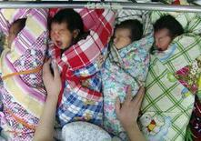 <p>Un'infermiera si prende cura di alcuni neonati nell'ospedale di Xiangfan, nella provincia cinese di Hubei. REUTERS/China Daily</p>