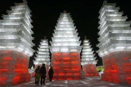 Tourists walk past a giant ice sculpture of the pagodas at the Ice and Snow World in Harbin, Heilongjiang province, January 5, 2008. REUTERS/Aly Song