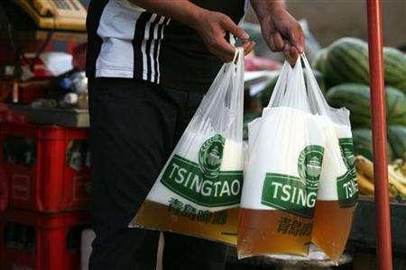 A man buys beer in plastic bags at a grocery shop in Qingdao, China's eastern province of Shandong, August 18, 2006. REUTERS/Nir Elias