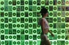 <p>Una ragazza passa vicino ad una parete tappezzata di cd. REUTERS/Issei Kato (JAPAN)</p>