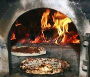 <p>La cottura di due pizze in un forno a legna. REUTERS/Paulo Whitaker</p>