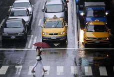 <p>Una donna attraversa la stada. REUTERS/Nicky Loh (TAIWAN)</p>