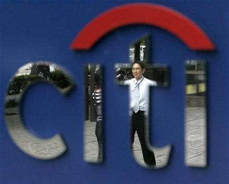 A man is reflected in the Citibank logo in Tokyo November 5, 2007. Citigroup Inc, JP Morgan Chase & Co and Morgan Stanley will form ''The Carbon Principles,'' climate change guidelines for advisors and lenders to power companies in the United States.
