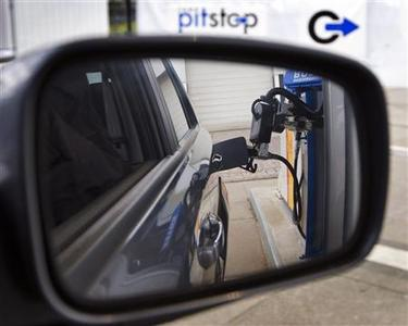 A car-fuelling robot is seen in the rear view mirror of a car in Emmeloord, central Netherlands, February 4, 2008. REUTERS/Michael Kooren