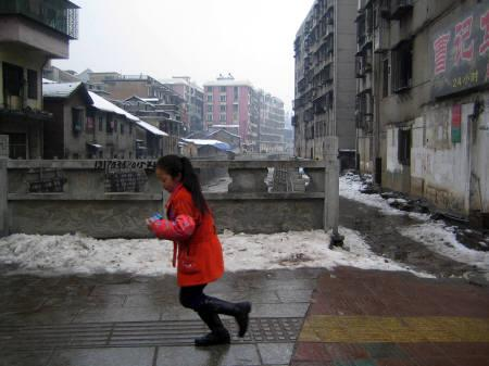 A girl runs past a street in Chenzhou in China's southern Hunan province February 4, 2008. REUTERS/John Ruwitch