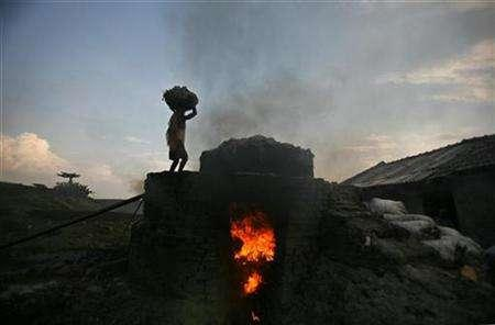 A labourer walks up a burning oven to make fertilizer ingredients out of scrap leather at a roadside factory in Kolkata May 4, 2007. India, one of the world's worst polluters that faces catastrophic impacts from climate change, must identify areas in its booming economy where clean technology could be used, a top U.N. climate official said on Wednesday. REUTERS/Parth Sanyal