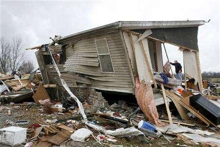 A man inspects his damaged house after tornadoes hit Lafayette, Tennessee, February 6, 2008. REUTERS/Josh Anderson