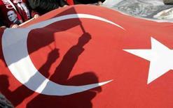 <p>Le ombre di alcuni dimostranti si riflettono sulla bandiera nazionale turca nel corso di una manifestazione a supporto del bando sul velo islamico nelle università. REUTERS/Umit Bektas (TURKEY)</p>