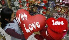 <p>Una ragazza con dei cusini a forma di cuore in un negozio indiano. REUTERS/Rupak De Chowdhuri (INDIA)</p>